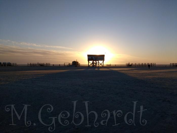 Die untergehende Sonne steht hinter einer Hütte auf Pfählen